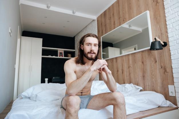 ベッドの上に座っているハンサムなひげを生やした若い男 無料写真