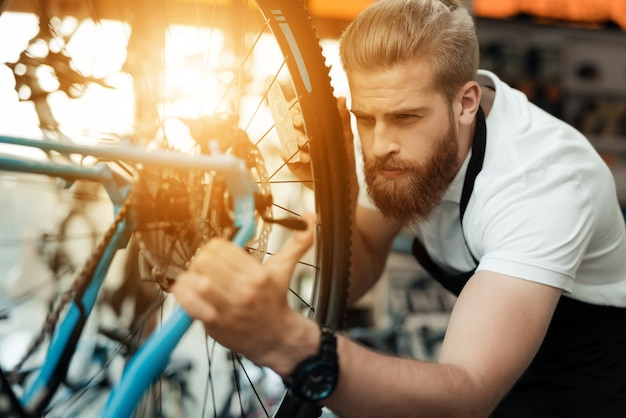 Handsome bike mechanic repair bicycle in workshop Premium Photo