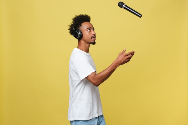 Handsome black man throwing a microphone and singing. Premium Photo