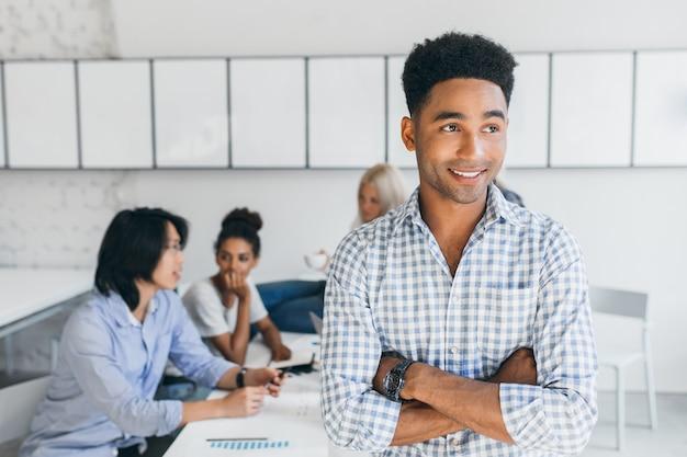 그의 동료는 새로운 아이디어를 논의하는 동안 멀리 찾고 손목 시계에 잘 생긴 흑인 젊은 남자. 아프리카 남자와 국제 It 전문가의 실내 초상화. 무료 사진