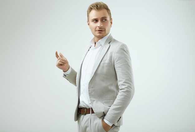 Handsome blonde man model in a fashion gray suit in studio Premium Photo