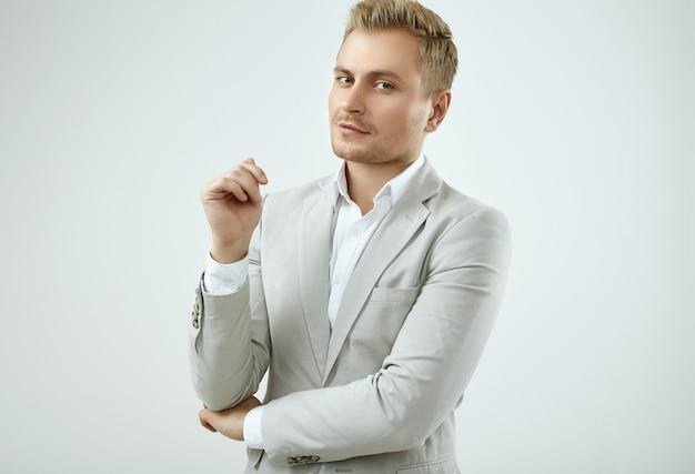 Handsome blonde man model in a fashion gray suit in studio Premium Photo