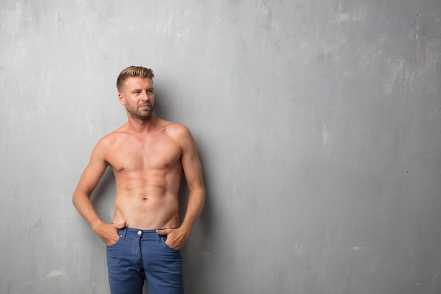 Handsome blonde man and nude torso over a grunge wall texture Premium Photo