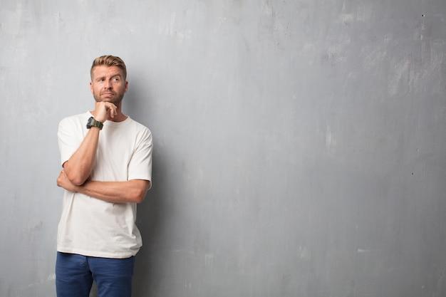 Handsome blonde man thinking against a grunge wall Premium Photo