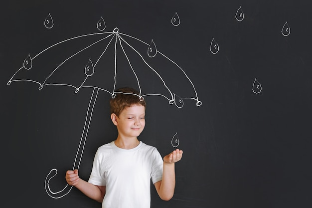 Handsome boy under chalk drawing umbrella Premium Photo