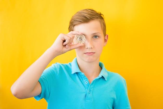 ハンサムな男の子はガラスプリズムを通して見えます。医療、ビジョン、埋め込みのコンセプト Premium写真