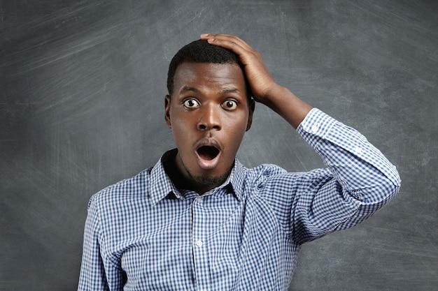 Bel cliente africano dagli occhi di bug che ha un'espressione smemorata, tiene la mano sulla testa, tiene la bocca spalancata, sembra sorpreso e spaventato, improvvisamente ricordando le grandi vendite nei negozi Foto Gratuite