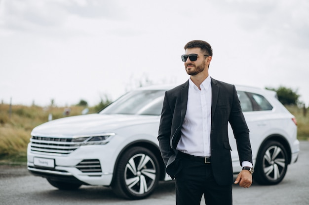 Handsome business man by the white car Free Photo