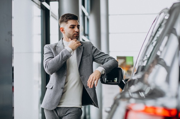 Handsome business man choosing a car in a car showroom Free Photo