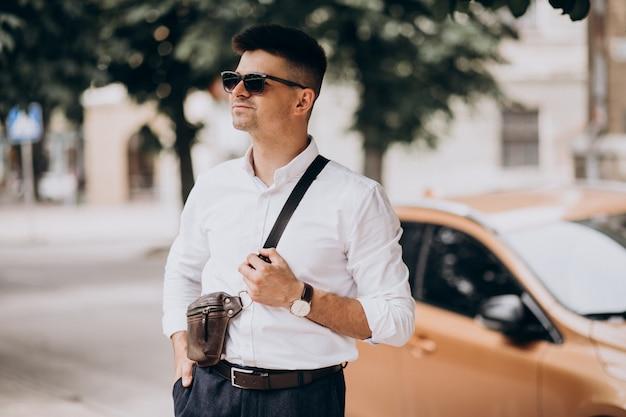 出張で彼の車のそばに立っているハンサムな実業家 無料写真