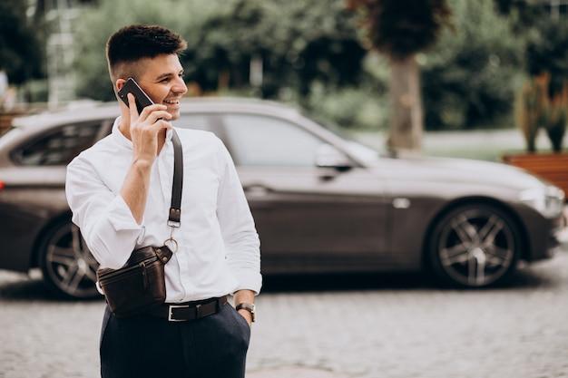 彼の車で電話で話しているハンサムなビジネスの男性 無料写真