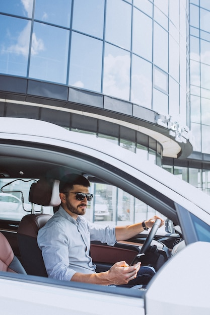 Handsome business man using phone in car Free Photo