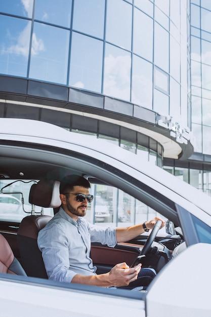 車で携帯電話を使用してハンサムな実業家 無料写真