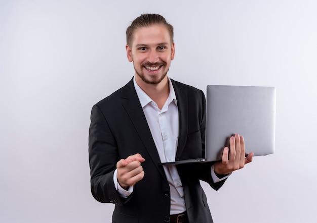 Красивый деловой человек в костюме, держащий портативный компьютер, указывая пальцем на камеру, весело улыбаясь, стоя на белом фоне Бесплатные Фотографии