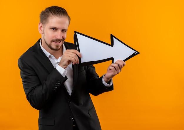 Bel uomo d'affari che indossa tuta tenendo la freccia bianca guardando la telecamera sorridendo e ammiccando in piedi su sfondo arancione Foto Gratuite