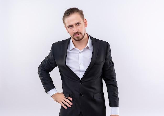 白い背景の上に立っている真剣な自信を持ってカメラを見てスーツを着ているハンサムなビジネスマン 無料写真