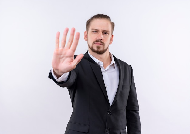 Красивый деловой человек в костюме делает знак остановки с открытой рукой, глядя в камеру с серьезным лицом, стоящим на белом фоне Бесплатные Фотографии