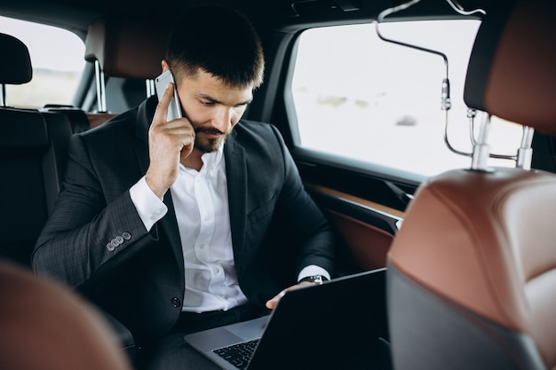 Handsome business man working on a computer in car Free Photo