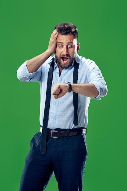 緑に分離された彼の腕時計をチェックするハンサムなビジネスマン 無料写真