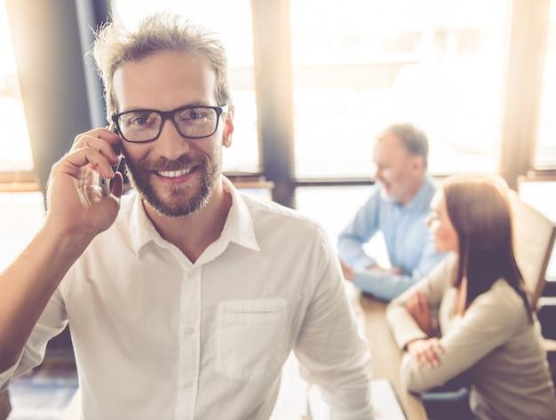 Красивый бизнесмен в очки разговаривает. Premium Фотографии