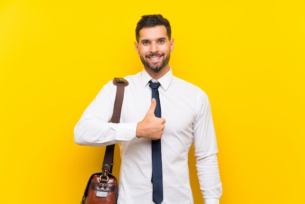 Handsome businessman over isolated yellow wall giving a thumbs up gesture Premium Photo