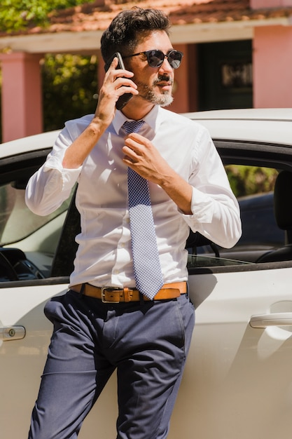 Handsome businessman standing near his car talking on mobile phone Free Photo