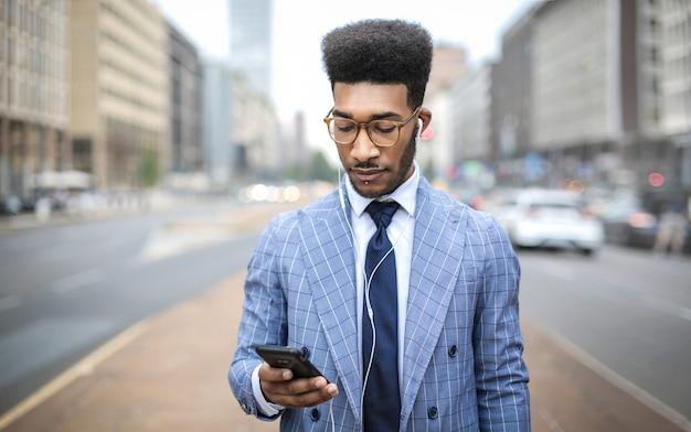 イヤホンを使用して彼の電話で呼び出すハンサムなビジネスマン Premium写真
