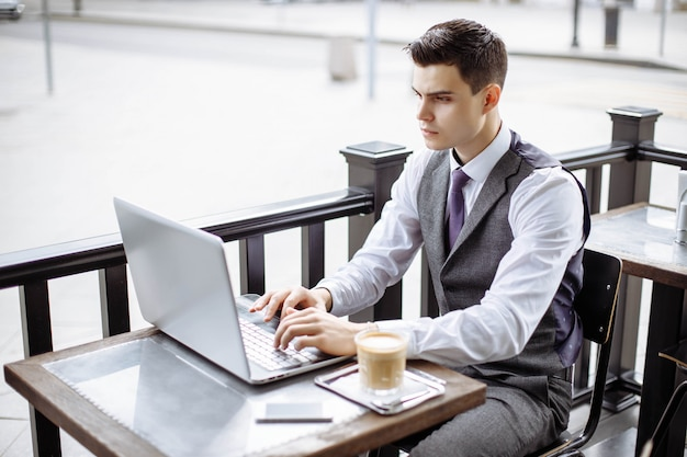 Handsome businessman wearing suit and using modern laptop outdoors Premium Photo