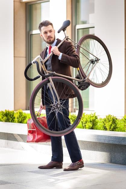 街の通りで彼の自転車を運ぶ赤いバッグでハンサムな実業家。 無料写真