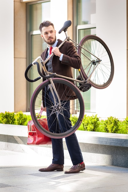 Handsome businessman with a red bag carrying his bicycle on city streets. Free Photo