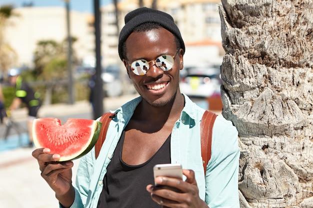 Selfieのポーズ、スイカのスライスで屋外に立って、ヤシの木にもたれかかってスタイリッシュな都会の摩耗でハンサムな屈託のない黒の旅行者、電話の画面がミラーレンズシェードに反映されています 無料写真
