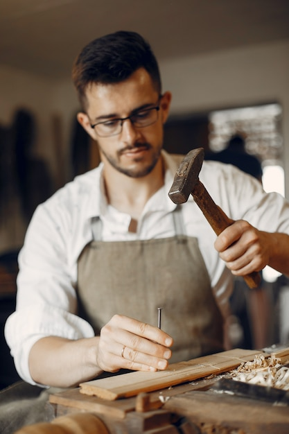 Handsome carpenter working with a wood Free Photo