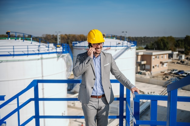 Красивый кавказский бизнесмен в костюме и с шлемом на голове говоря на телефоне пока стоящ outdoors. на заднем плане находятся резервуары для хранения нефти. Premium Фотографии