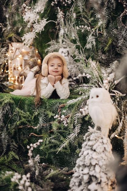 Bel bambino caucasico con lunghi capelli biondi si trova nell'atmosfera natalizia con molti alberi decorati intorno a lei e il gufo Foto Gratuite