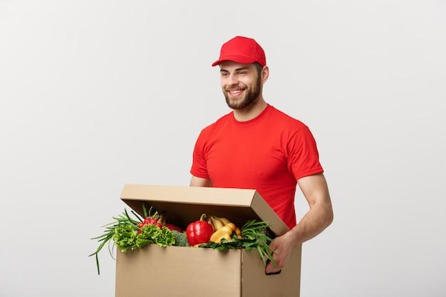 新鮮な果物と野菜の食料品ボックスで赤い制服を着たハンサムな白人食料品配達宅配便男 Premium写真