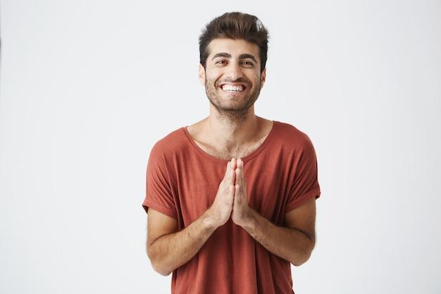 友達からの誕生日プレゼントで驚いた幸せそうに笑って手をたたく赤いtシャツでハンサムな白人男性。肯定的な雰囲気を共有するひげを剃っていない男のポートレート、クローズアップ。 無料写真