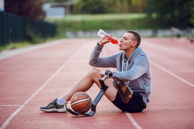 ハンサムな白人のスポーティな障害者のスポーツウェアの競馬場の上に座って、飲み物を飲みます。足の間はバスケットボールです。 Premium写真
