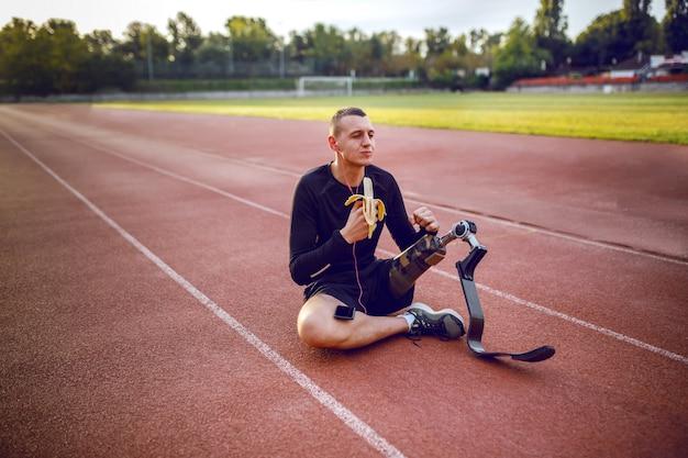 ハンサムな白人のスポーティな障害を持つ若い男のスポーツウェアと競馬場に座って、音楽を聴いて、バナナを食べる義足。 Premium写真
