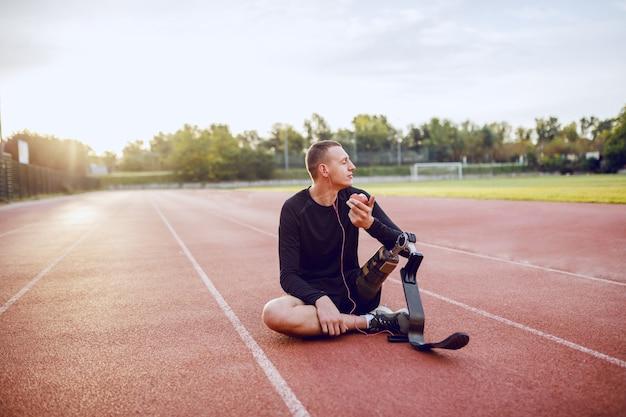 ハンサムな白人のスポーティな障害を持つ若い男のスポーツウェアと人工脚の競馬場の上に座って、音楽を聴くと食用リンゴ。 Premium写真