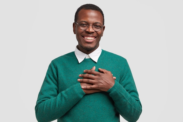 Handsome cheerful black man keeps both hands on chest, feels touched or thankful, smiles broadly, wears elegant green sweater Free Photo