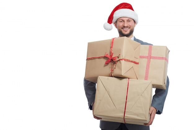 分離された笑顔のラップされたクリスマスプレゼントの山を保持しているハンサムな陽気な青年実業家 無料写真