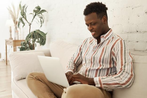 노트북 컴퓨터와 소파에 앉아 집에서 일을 즐기는 잘 생긴 쾌활한 젊은 어두운 피부 남성 Smm 관리자 무료 사진