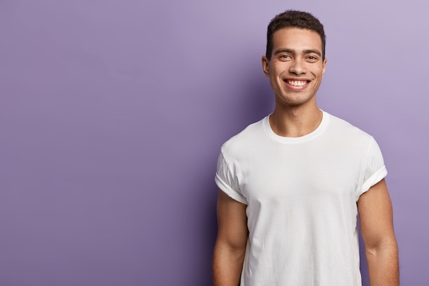 Handsome cheerful young sportsman has sporty body, muscular arms, wears white mock up t shirt, has short dark hair, toothy appealing smile, stands over purple wall, blank copy space aside Free Photo