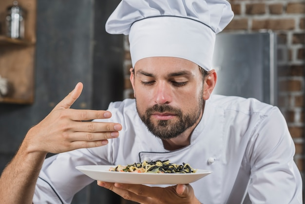 Handsome chef sniffing smell of cooked dish Free Photo