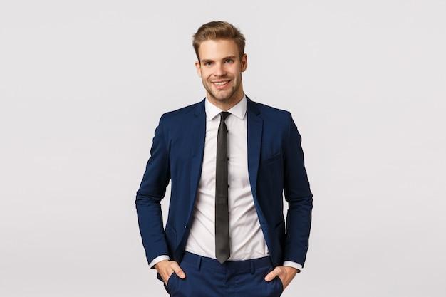 ハンサムな自信を持って金髪のひげを生やした実業家、ポケットに手を繋いで、嬉しそうに笑って、プロの雰囲気を与え、ビジネスについて議論し、彼の収入を2倍にし、成功、白い背景 Premium写真