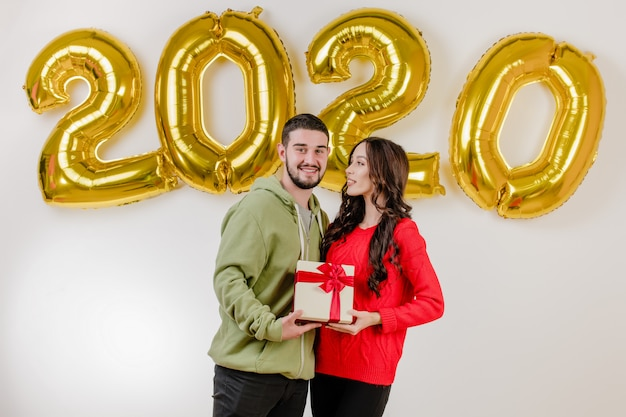 Handsome couple man and woman with christmas present in front of 2020 new year balloons Premium Photo