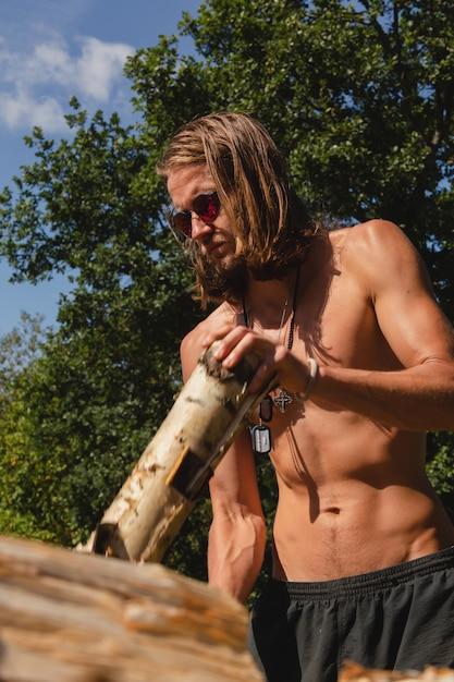 裸の胴体を持つハンサムなクリナイト男が田舎で木材を分割します。 Premium写真