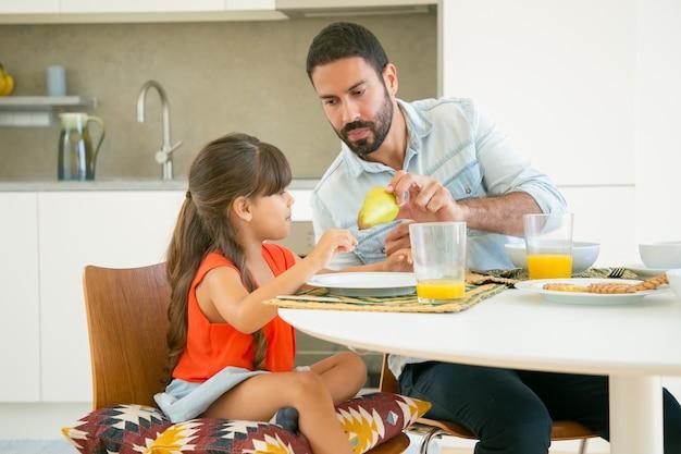 彼らが台所で一緒に朝食をとりながら彼の女の子に果物を与えるハンサムなお父さん 無料写真
