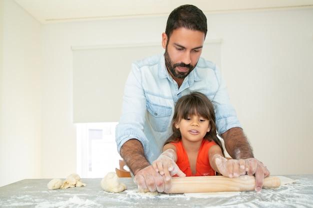 ハンサムなお父さんが娘を焼くように教えています。 無料写真