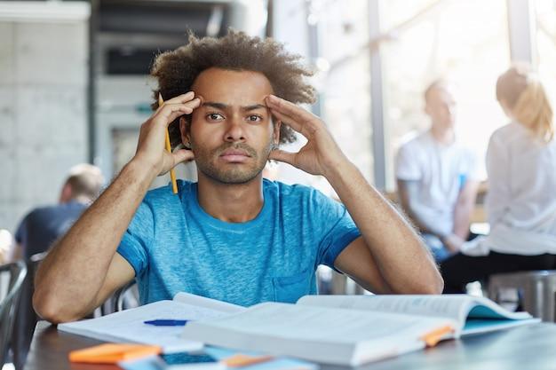 Bello studente barbuto dalla pelle scura con taglio di capelli afro che stringe le tempie, avendo mal di testa mentre si prepara per esami o test notte e giorno, guardando con espressione dolorosa e frustrata Foto Gratuite
